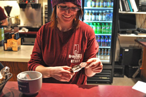 Photos by Emily Hoffmann. Hannah St. Aubin, a senior and Brewhaus employee, puts a hole in a student's Brewhaus Beer Tour punch card.
