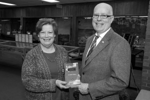 Photo by Doug Moore. Chancellor Patterson presents professor Kathy Davis, the director of the library, with President Kevin Reilly's retirement book.
