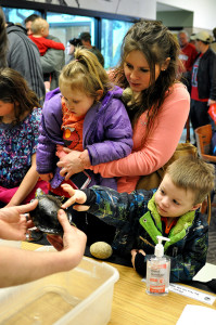 Photo by Emily Hoffmann. Stevens Point locals Emily Longo, Jojo Longo, and Micah Grey learn about painted turtles.