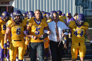 Head coach Tom Journell locks arms with his players as they enter the field. Photo by Jack McLaughlin.