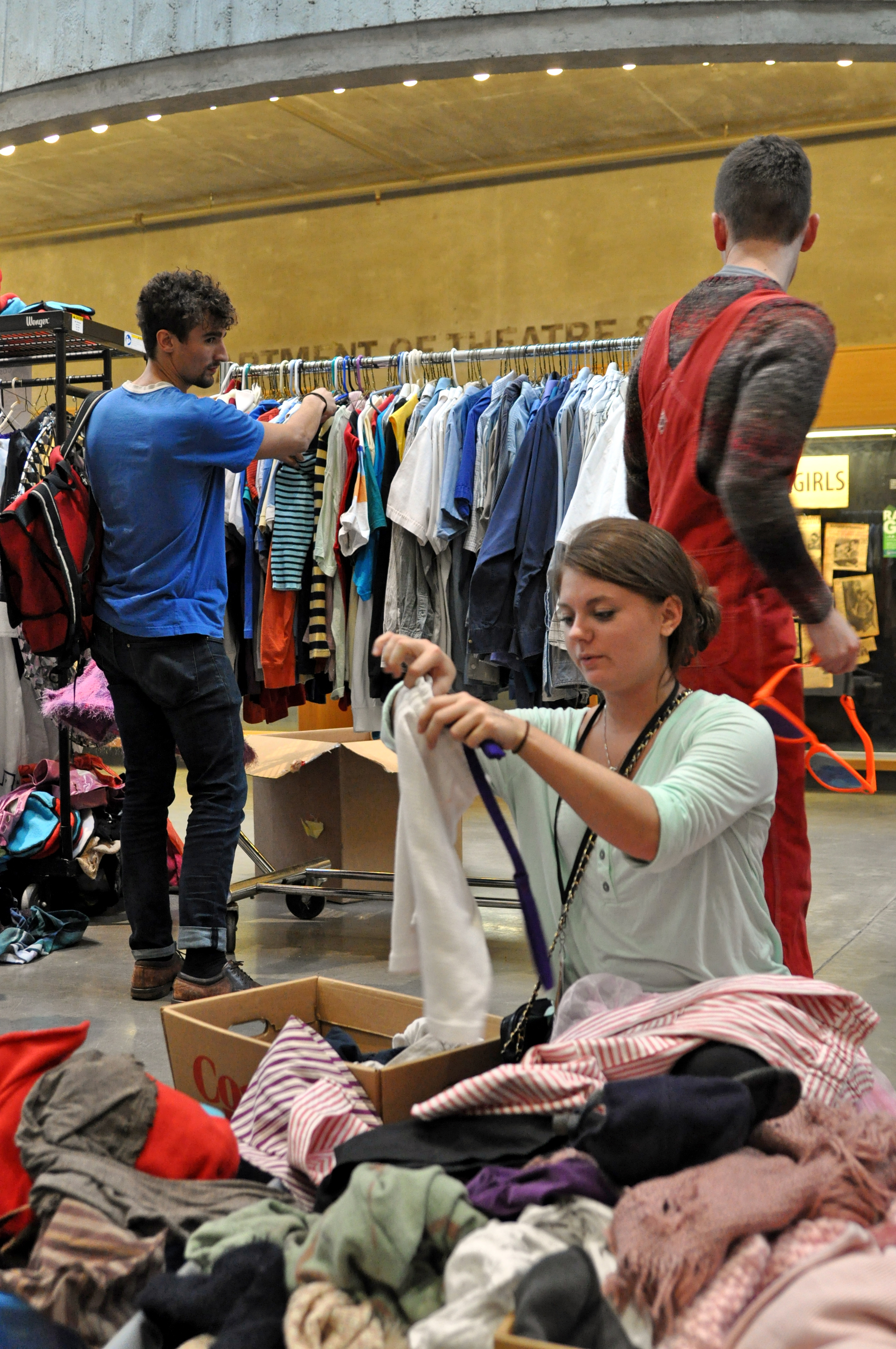 Allison Kelley, junior, looks through a box of costumes at the costume sale in the NFAC. Photo by Emily Hoffmann.