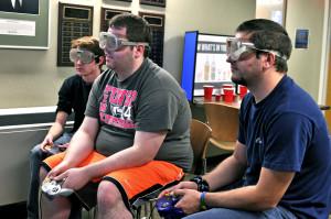 Joey Montaine, freshman, Kevin Martin and Chris Cleworth, juniors, wear drunk goggles while playing Mario Kart to simulate drunk driving. Photo by Emily Hoffmann.