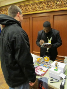 LeRoy Butler signs memorabilia and speaks to students. Photo by Becky Vosters.