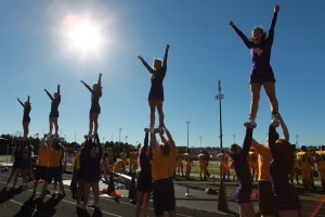 The cheer and stunt team performs during a football game. Photo by Paula Lauer.
