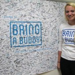 Jenna Furger with the UWSP Bring A Buddy banner, where over 1,500 students have pledged. Photo courtesy of wixx.com