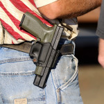 In this Oct. 9, 2015 file, Michael Johnson wears a firearm as he waits outside of Roseburg Municipal Airport for President Barack Obama's arrival in Roseburg, Ore. Voters in a southern Oregon county will weigh in next month on a measure that seeks to prohibit enforcement of gun laws, although it may have only symbolic effect.   Courtesy of AP Photo, Ryan Kang
