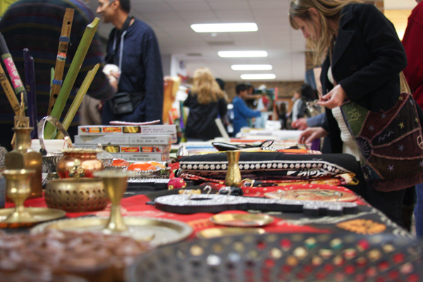 A festival attendee looks through the goods for sale at  a vendor's table. Photos by Emmitt Williams.