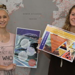 UWSP students Melanie Heibler and Emily Tauschek pose in front of the floor to ceiling world map in the new Office of International Education. Photo by Kylie Bridenhagen.