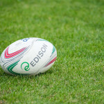 "A rugby ball sits on a field. ""Cus Torino-Lions Piacenza7"" by Max is licensed under CC BY-NC-ND 2.0."