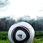 "A soccer ball sitting on a field. ""Central Park – Adidas Soccer Ball"" by Joe Solo is licensed under CC BY 2.0."